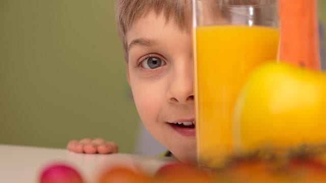 boy with face behind glass of orange juice