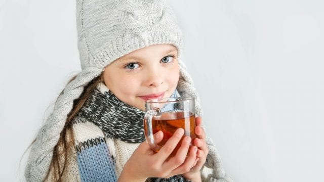 young girl in beanie with hot tea