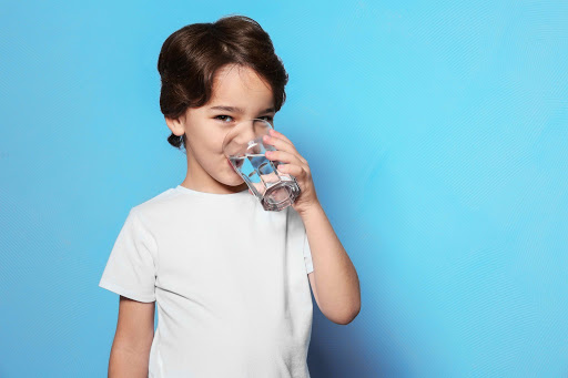 boy on blue background drinking water