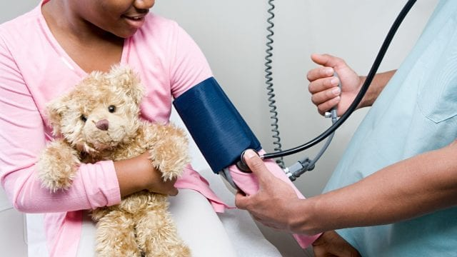 Child holding teddy bear getting their blood pressure read by a doctor