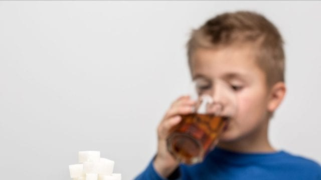 Child drinking soda behind stacked sugar cubes