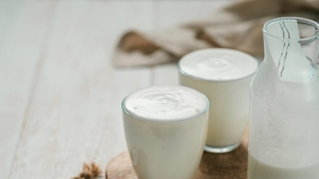 Two glasses of white kefir and a half full pitcher of kefir on a wooden cutting board