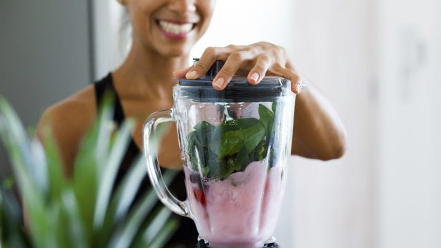 Woman making a colorful smoothie