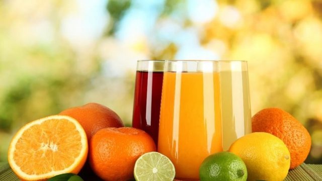 Fruit juice in clear glasses next to citrus